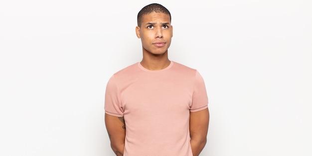 Młody czarny mężczyzna wyglądający na zdziwionego i zdezorientowanego, zastanawiający się lub próbujący rozwiązać problem lub myślący