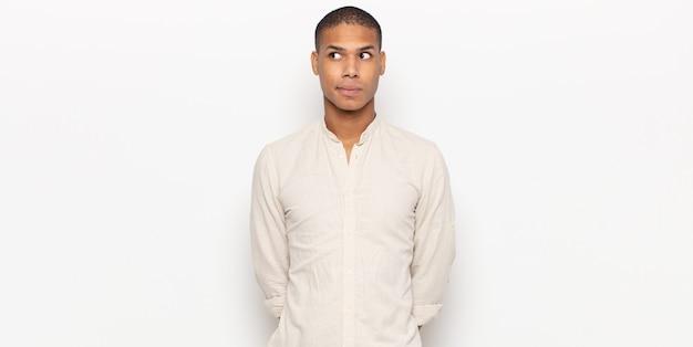 Młody czarny mężczyzna wyglądający na zmartwionego, zestresowanego, niespokojnego i przestraszonego, spanikowanego i zaciskającego zęby