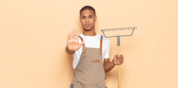 Młody czarny mężczyzna wyglądający poważnie, surowo, niezadowolony i zły pokazując otwartą dłoń, wykonując gest zatrzymania