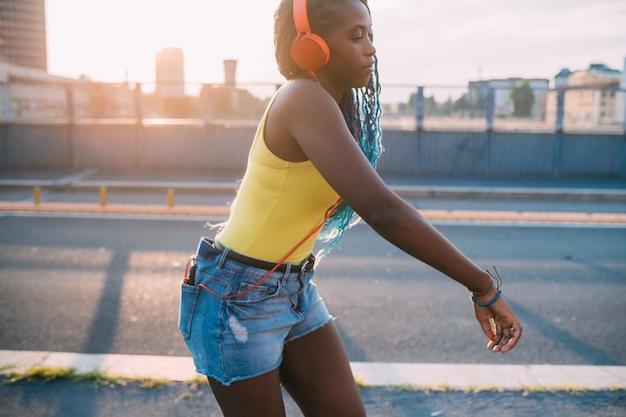 Młody czarny pięknej kobiety plenerowy słuchający muzyczny taniec