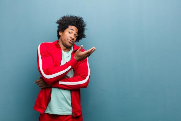 Młody czarny sportowiec czuje się zdezorientowany i nieświadomy, zastanawiając się nad wątpliwym wytłumaczeniem lub myślą o ścianie grunge