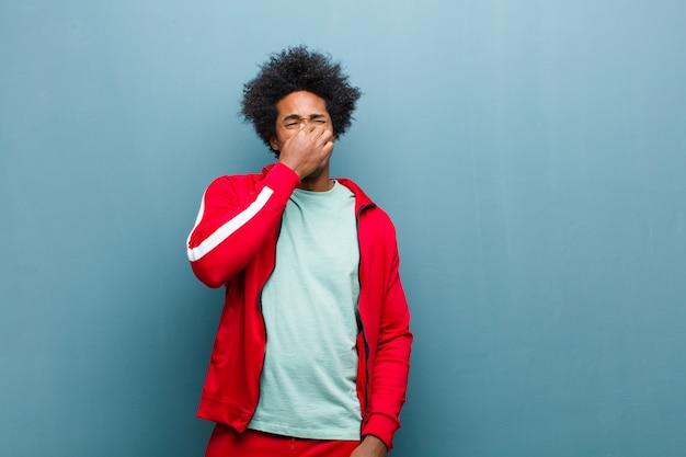 Młody czarny sportowiec czuje się zniesmaczony, trzymając nos, aby nie poczuć nieprzyjemnego i nieprzyjemnego smrodu na ścianie grunge