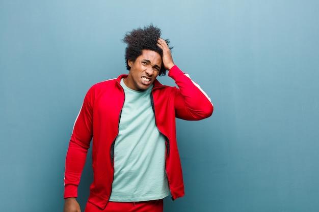 Młody czarny sportowiec panikuje nad zapomnianym terminem, czuje się zestresowany, musi ukryć bałagan lub błąd na ścianie grunge