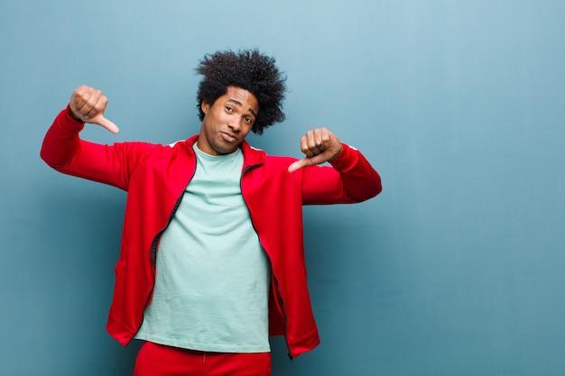 Młody czarny sportowiec wyglądający na smutnego, rozczarowanego lub wściekłego, pokazujący kciuk w nieporozumieniu, czujący się sfrustrowany na ścianie grunge