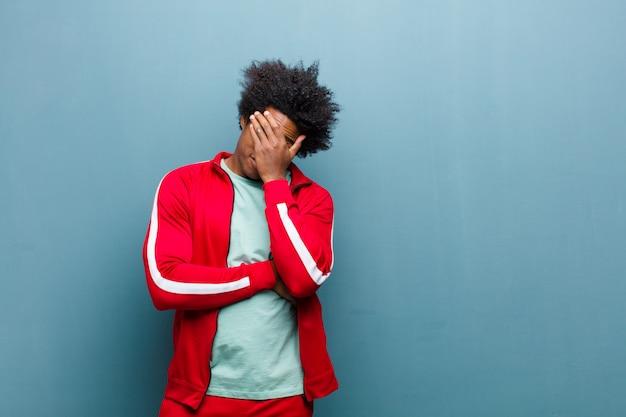 Młody czarny sportowiec wyglądający na zestresowanego, zawstydzonego lub zdenerwowanego, z bólem głowy, zakrywający twarz dłonią