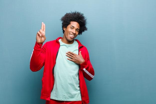 Młody czarny sportowiec wyglądający szczęśliwy, pewny siebie i godny zaufania, uśmiechnięty i pokazujący znak zwycięstwa, z pozytywnym nastawieniem do ściany grunge