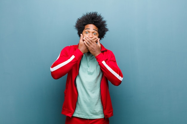 Młody czarny sportowiec zakrywający usta dłońmi z zszokowanym, zdziwionym wyrazem, trzymający w tajemnicy lub mówiąc: ups przed ścianą grunge