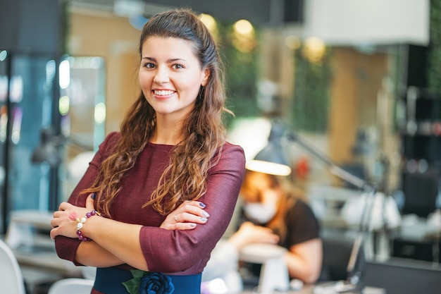 Młody czarujący uśmiechnięty kobieta właściciel salonu piękności gwoździa bar, pojęcie własny mały biznes