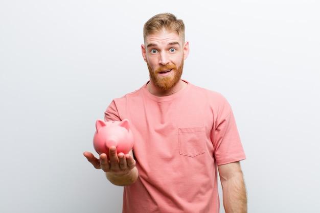 Młody czerwieni głowy mężczyzna trzyma prosiątko banka biel
