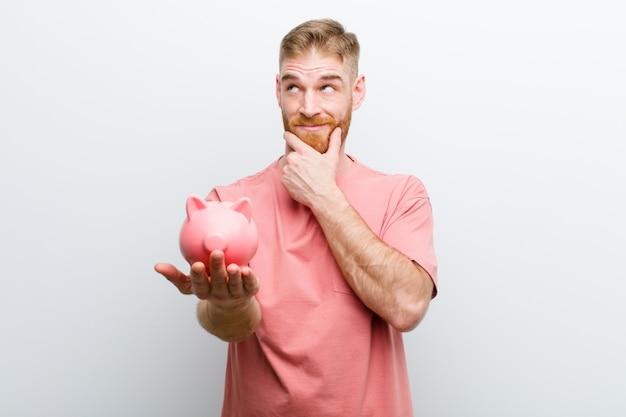 Młody czerwieni głowy mężczyzna trzyma prosiątko banka przeciw białemu tłu