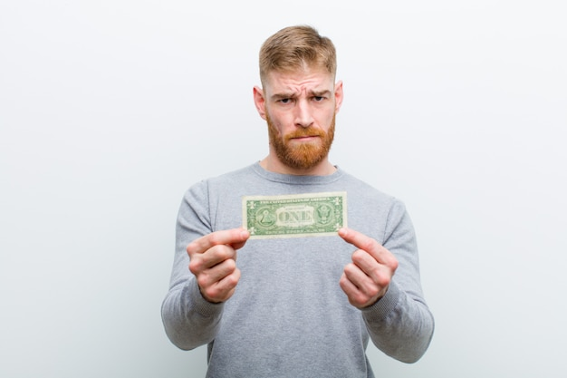 Młody czerwieni głowy mężczyzna z dolarami białymi