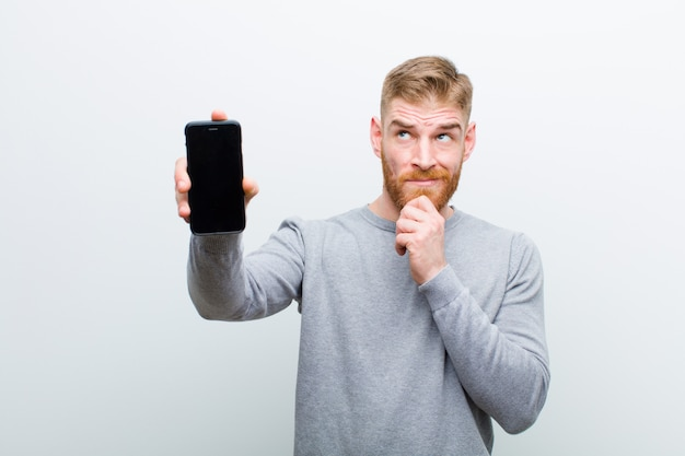 Młody czerwonej głowy mężczyzna z mądrze telefonem przeciw białemu tłu