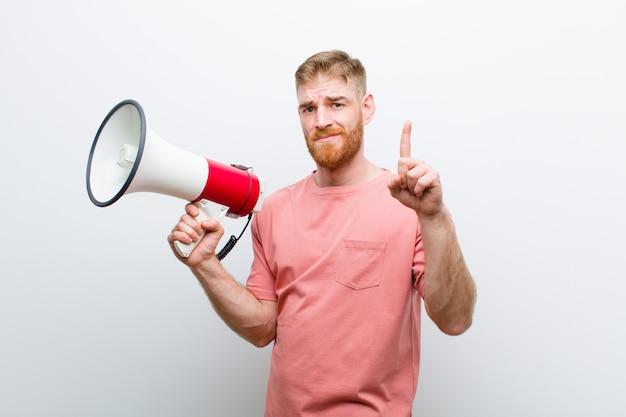 Młody czerwonej głowy mężczyzna z megafonem przeciw białemu tłu