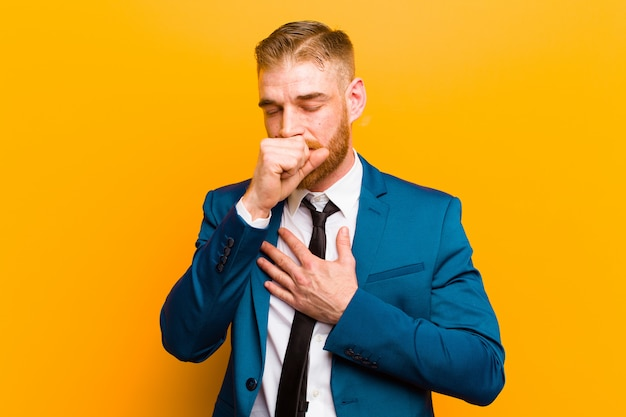 Młody czerwony biznesmen głowy czuje się chory z bólem gardła i objawami grypy, kaszel z usta pokryte