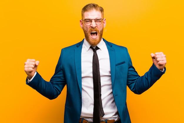 Młody czerwony biznesmen głowy krzyczy agresywnie z gniewnym wyrazem twarzy lub zaciśniętymi pięściami świętując sukces na pomarańczowo