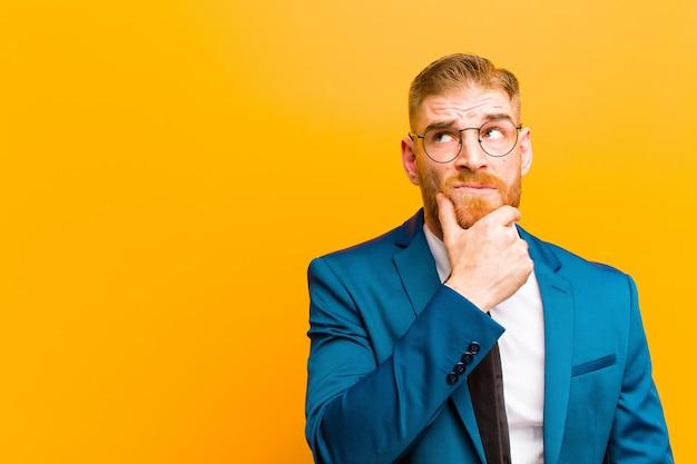 Młody czerwony biznesmen głowy myśli, czując się niepewnie i zdezorientowany, z różnymi opcjami, zastanawiając się, którą decyzję podjąć przeciwko pomarańczowy