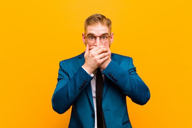 Młody czerwony biznesmen głowy obejmujący usta z zszokowanym, zaskoczonym wyrazem twarzy, trzymając w tajemnicy lub mówiąc: ups przeciwko pomarańczy