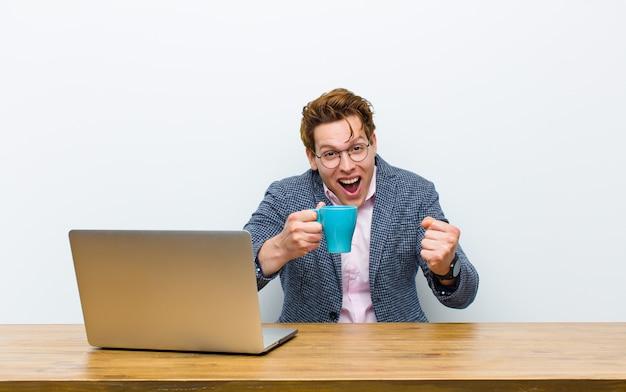 Młody czerwony biznesmen głowy pracuje w swoim biurku z filiżanką gorącej kawy
