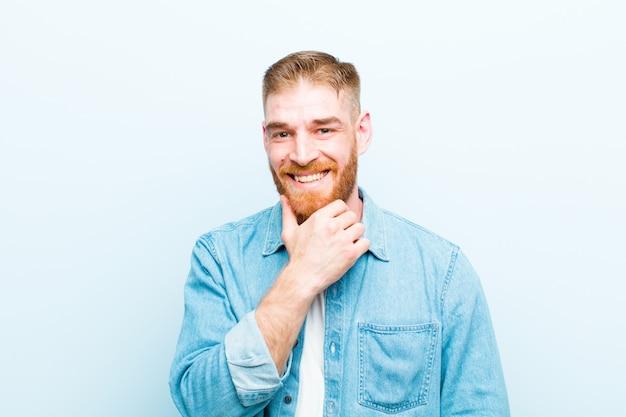 Młody czerwony głowa mężczyzna uśmiecha się, ciesząc się życiem, czując się szczęśliwy, przyjazny, zadowolony i beztroski z ręką na brodzie na miękkim niebieskim tle