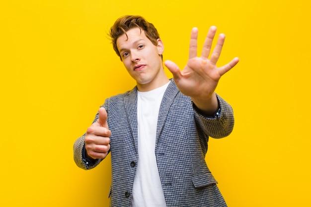 Młody czerwony głowa mężczyzna uśmiecha się i szuka przyjazny, pokazując numer sześć lub szósty ręką do przodu, odliczając na pomarańczowym tle
