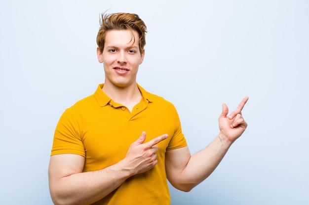 Młody czerwony głowa mężczyzna uśmiecha się radośnie i wskazując na bok i do góry z obu rąk pokazując obiekt w przestrzeni kopii na niebieską ścianą