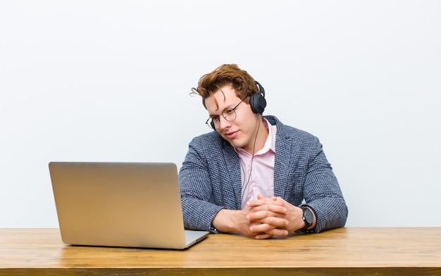 Młody czerwony kierowniczy biznesmen pracuje w jego biurku z hełmofonami