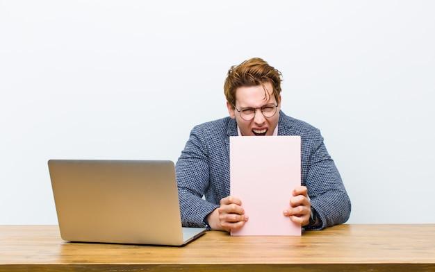 Młody czerwony kierowniczy biznesmen pracuje w jego biurku z książką