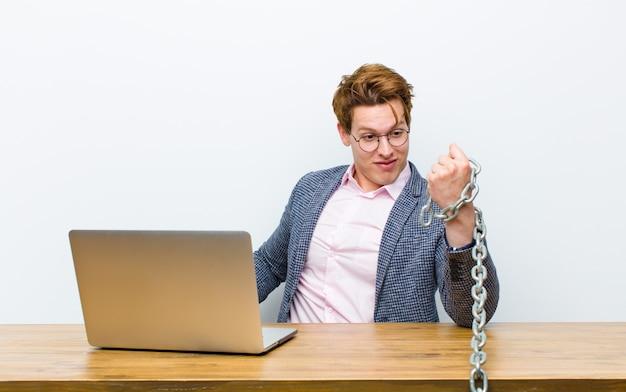 Młody czerwony kierowniczy biznesmen pracuje w jego biurku z łańcuchem