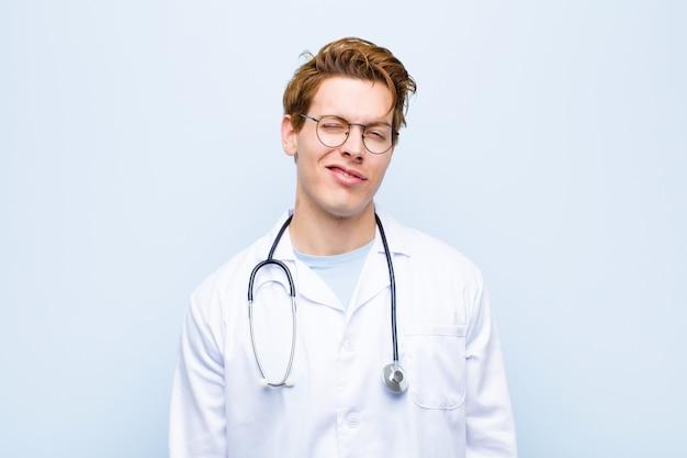Młody czerwony lekarz lekarz patrząc szczęśliwy i przyjazny, uśmiechając się i mrugając okiem