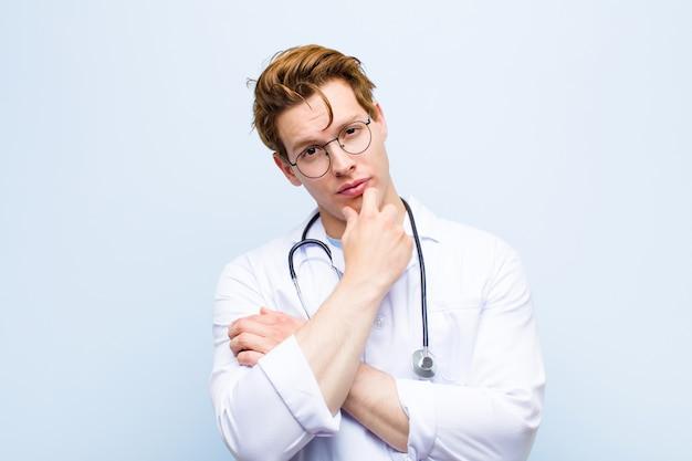 Młody czerwony lekarz lekarz szuka poważnego, zmieszanego, niepewnego i zamyślonego