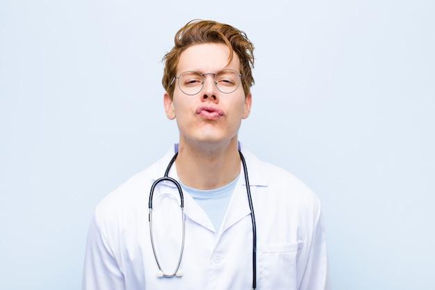 Młody czerwony lekarz naciska usta wraz ze słodkim, zabawnym, radosnym i uroczym wyrazem twarzy, wysyłając buziaka na niebieską ścianę