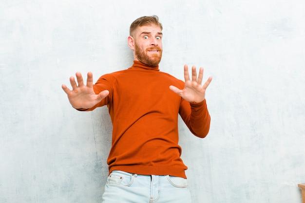 Młody czerwony mężczyzna noszący szyję żółwia czuje się oszołomiony i przestraszony, obawiając się czegoś przerażającego, z otwartymi rękami z przodu mówiąc: trzymaj się z dala od cementowej ściany