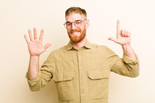 Młody czerwony mężczyzna uśmiecha się i wygląda przyjaźnie, pokazuje numer siedem lub siódmy z ręką do przodu, odliczając do beżowej ściany