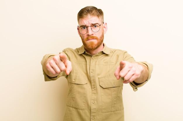 Młody czerwony mężczyzna wskazujący na aparat obiema palcami i gniewnym wyrazem, mówi ci, abyś wykonał swój obowiązek nad beżową ścianą