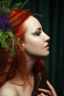 Młody czerwony model głowy pozuje z kreatywnym makijażem
