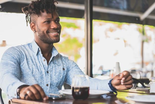 Młody człowiek african american czeka na lunch, siedząc w restauracji.