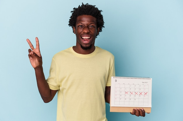 Młody człowiek african american gospodarstwa kalendarz na białym tle na niebieskim tle radosny i beztroski pokazując symbol pokoju palcami.