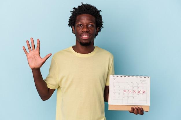 Młody człowiek african american gospodarstwa kalendarz na białym tle na niebieskim tle uśmiechający się wesoły wyświetlono numer pięć palcami.