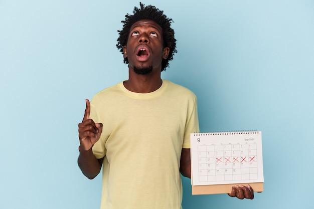 Młody człowiek african american gospodarstwa kalendarz na białym tle na niebieskim tle, wskazując do góry z otwartymi ustami.
