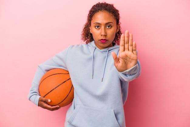 Młody człowiek african american, grając w koszykówkę na białym tle na różowym tle stojący z wyciągniętą ręką pokazując znak stop, uniemożliwiając.