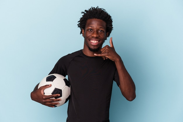 Młody człowiek african american, grając w piłkę nożną na białym tle na niebieskim tle pokazując gest połączenia z telefonu komórkowego palcami.