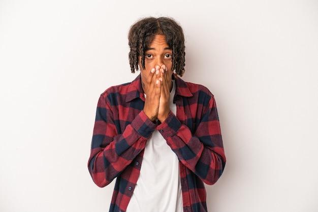 Młody człowiek african american na białym tle na białym tle obejmujące usta rękami patrząc zmartwiony.
