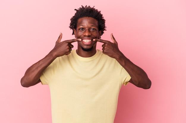 Młody człowiek african american na białym tle na różowym tle uśmiecha się, wskazując palcami na ustach.