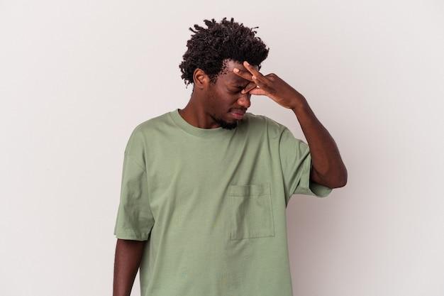 Młody człowiek african american na białym tle o ból głowy, dotykając przodu twarzy.