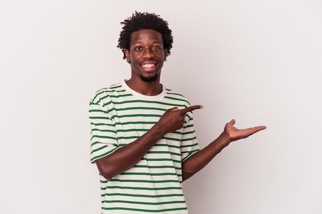 Młody człowiek african american na białym tle podekscytowany, trzymając miejsce na dłoni.