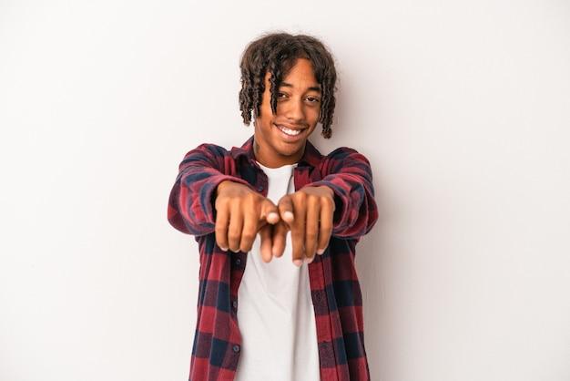 Młody człowiek african american na białym tle wskazując do przodu palcami.