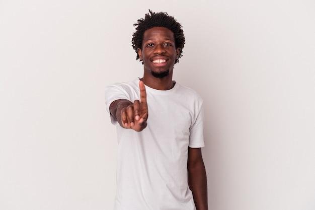 Młody człowiek african american na białym tle wyświetlono numer jeden z palcem.