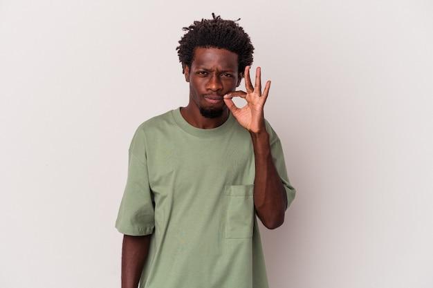 Młody człowiek african american na białym tle z palcami na ustach, zachowując tajemnicę.