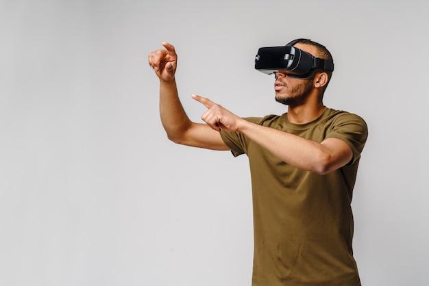 Młody człowiek african american noszenie zestawu słuchawkowego vr wirtualnej rzeczywistości na szarej ścianie