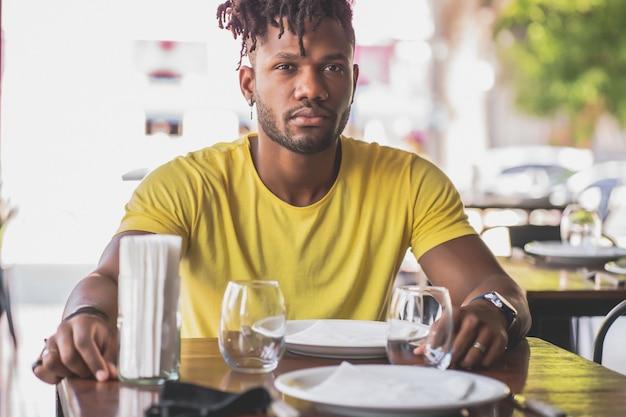 Młody człowiek african american, patrząc w kamerę, siedząc w restauracji.